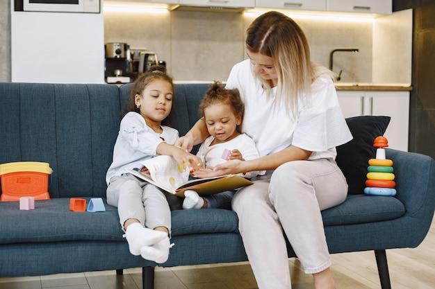 Moeder en kinderen ontspannen samen op de bank thuis in de woonkamer. kleine meisjes die een boek lezen.