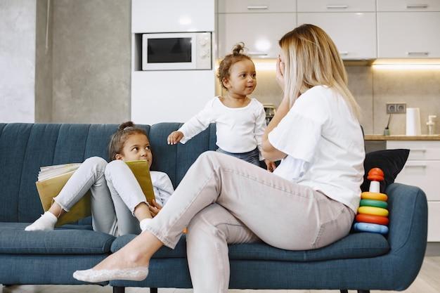 Moeder en kinderen ontspannen samen op de bank thuis in de woonkamer. kleine meisjes spelen met speelgoed en lezen een boek.