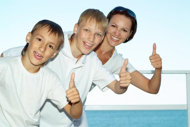 Moeder en kinderen op de achtergrond van de zee met duimen omhoog