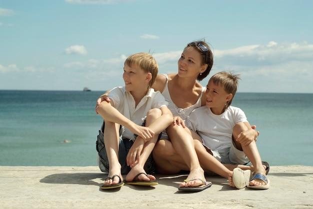 Moeder en kinderen op de achtergrond van de zee
