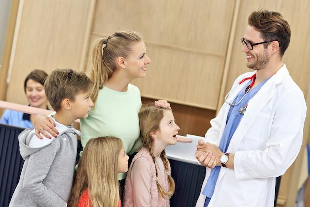 Moeder en kinderen samen in ziekenhuis met dokter