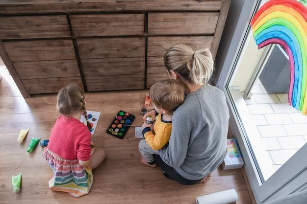 Moeder en kinderen schilderen een regenboog op het raam