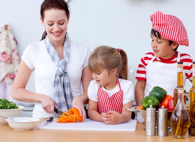 Moeder en kinderen snijden groenten in de keuken