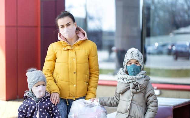 Moeder en kinderen staan op straat bij de winkel en dragen maskers tijdens quarantaine