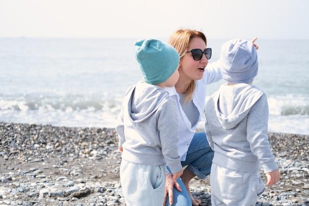 Moeder en kinderen twee jongens tweeling spelen met plezier op het strand in de lente of herfst