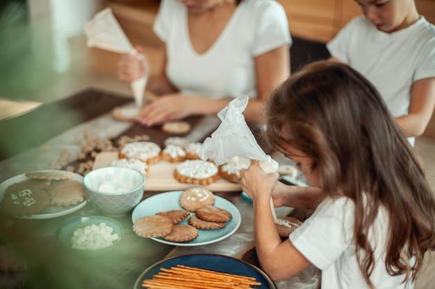 Moeder en kinderen versieren kerstkoekjes thuis. een jongen en een meisje schilderen met cornetten mee