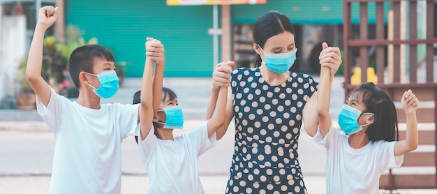 Moeder en kinderenfamilie die masker dragen om voor de gek te houden voor bescherm coronavirus