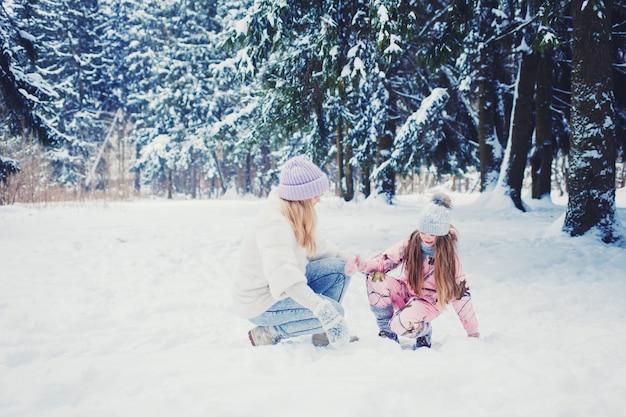 Moeder en kindmeisje op sneeuw de wintergang in aard