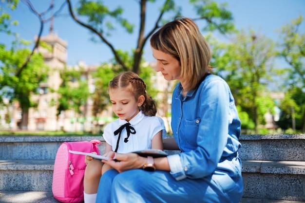 Moeder en klein kind dochter zittend op trappen en lees boek