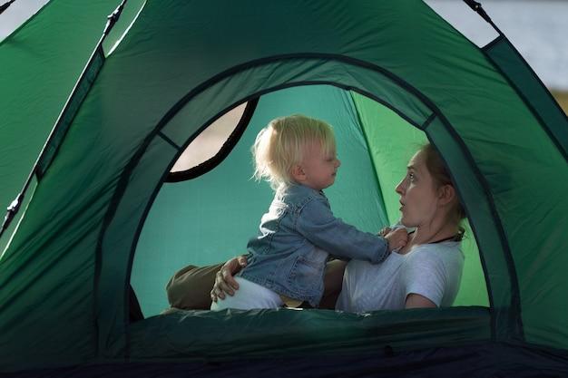 Moeder en klein kind in tent in de natuur