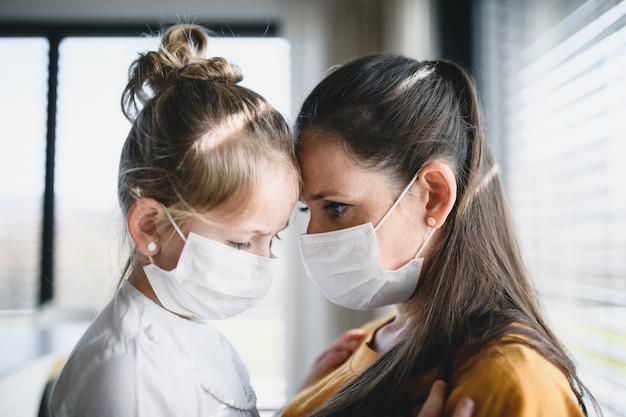 Moeder en klein kind met gezichtsmaskers binnenshuis praten thuis
