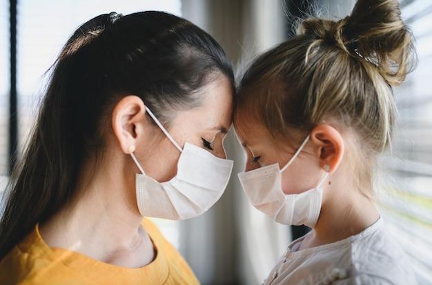 Moeder en klein kind met gezichtsmaskers binnenshuis, pratend. corona virus en quarantaine concept.