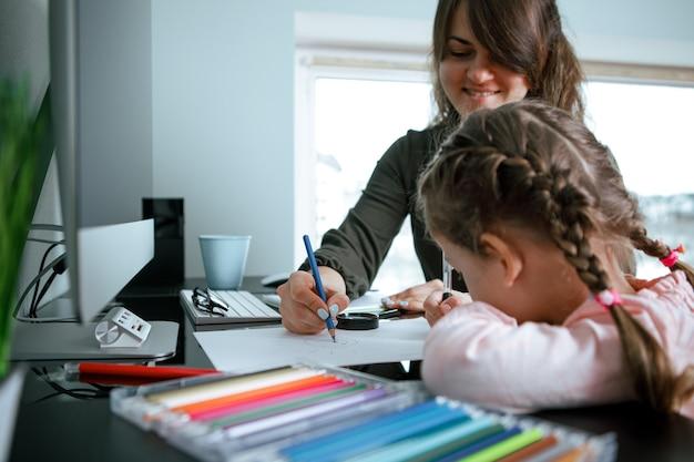 Moeder en klein meisje kleuren met kleurpotloden terwijl ze samen aan hun levende tafel zitten