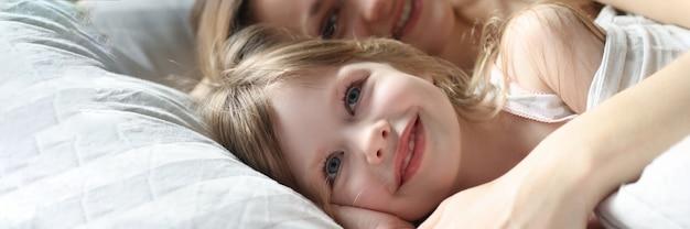 Moeder en klein meisje liggen in bed en knuffelen