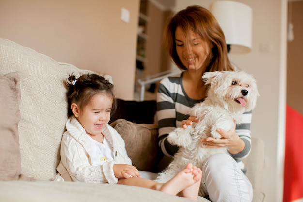 Moeder en klein meisje met hond in de kamer