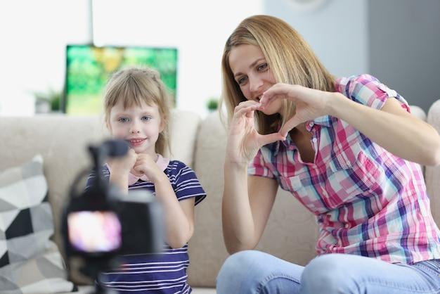 Moeder en klein meisje tonen hart met hun handen naar de camera