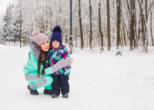 Moeder en klein peuter meisje wandelen in het winter woud en plezier met sneeuw. familie