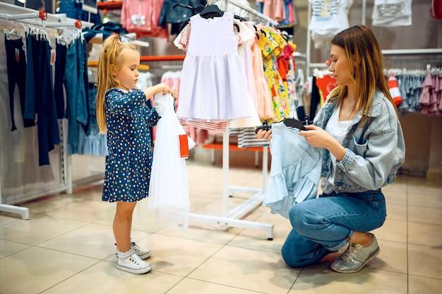 Moeder en kleine baby die jurk in de kinderwinkel kopen