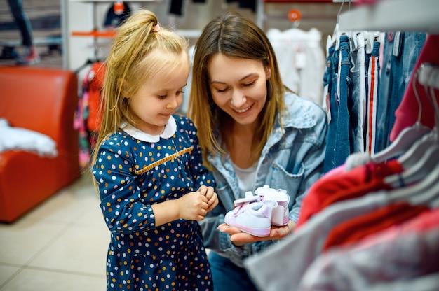 Moeder en kleine baby die kleren in de kinderwinkel kopen
