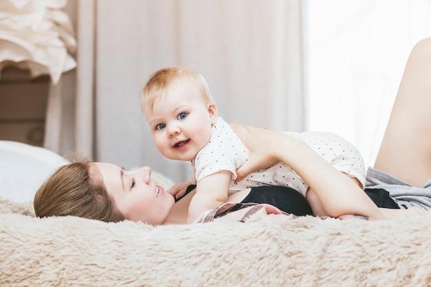 Moeder en kleine baby in bed en werden 's ochtends wakker en lachten thuis