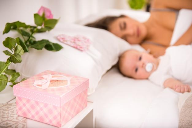 Moeder en kleine baby rusten in bed.