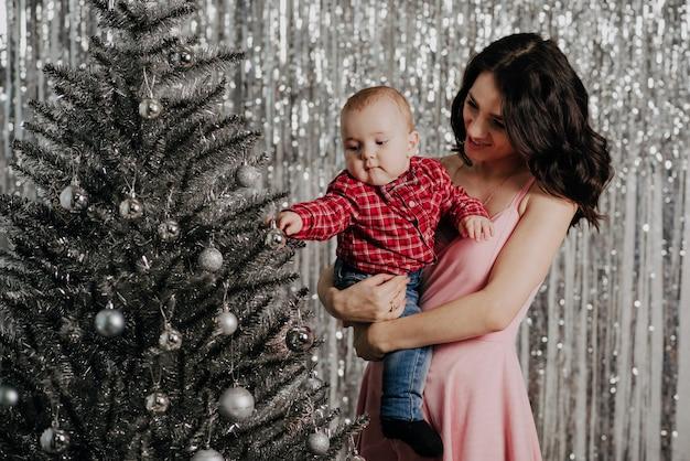 Moeder en kleine babyjongen op kerstboom achtergrond