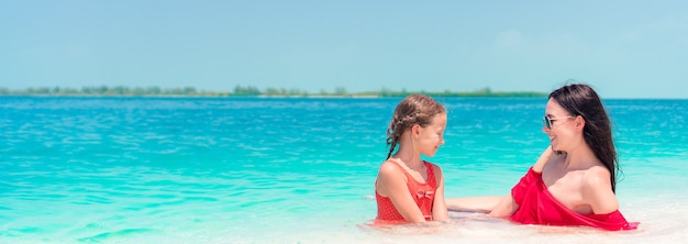 Moeder en kleine dochter die van tijd genieten bij tropisch strand