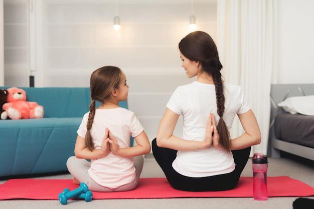 Moeder en kleine dochter doen gymnastiek op de mat