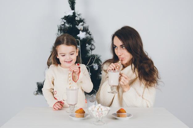 Moeder en kleine dochter drinken cacao met marshmallows