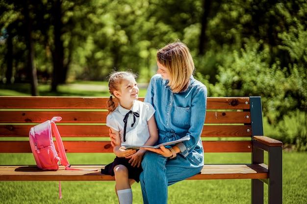 Moeder en kleine dochter in openbaar park zittend op de bank en kijken elkaar glimlachend. parenth