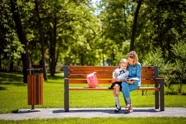 Moeder en kleine dochter in openlucht openbare parkzitting op de bank en het gelezen boek