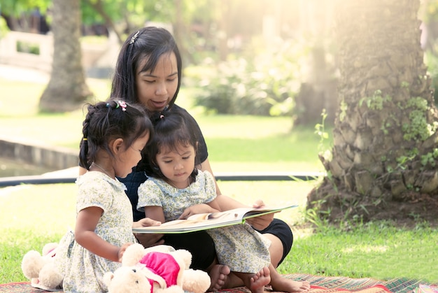 Moeder en kleine dochter leesboek samen in het park