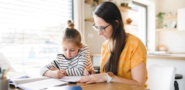 Moeder en kleine dochter leren binnenshuis thuis, corona-virus en quarantaineconcept.