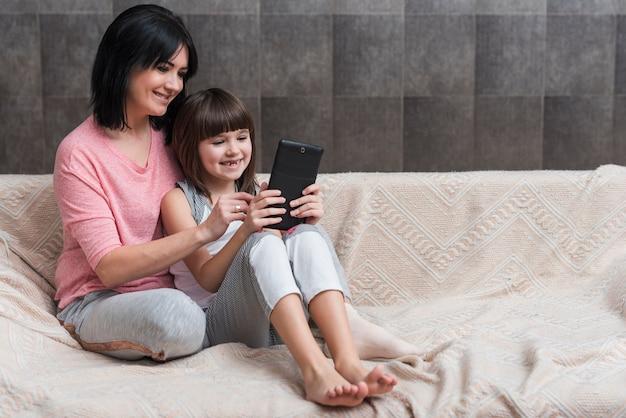 Moeder en kleine dochter met behulp van de tablet op de bank
