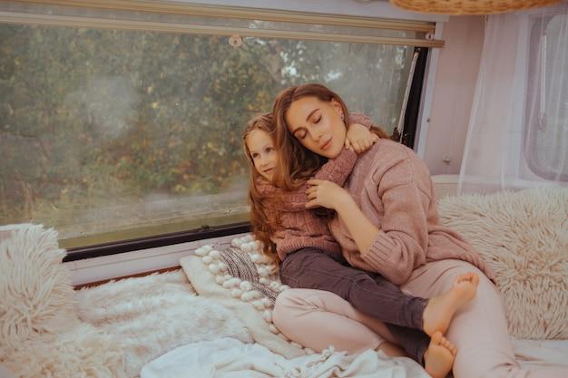 Moeder en kleine dochter ontspannen en plezier maken op het platteland in camper