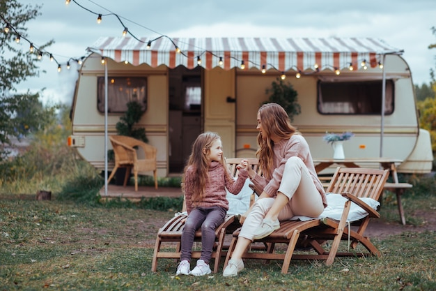 Moeder en kleine dochter ontspannen en plezier maken op het platteland op camper van vakantie