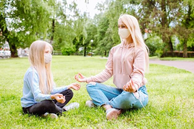 Moeder en kleine dochter op het park met beschermende maskers.