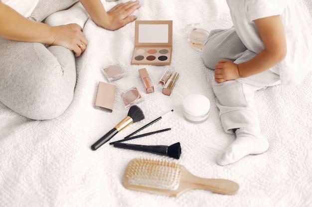 Moeder en kleine dochter plezier thuis met cosmetica