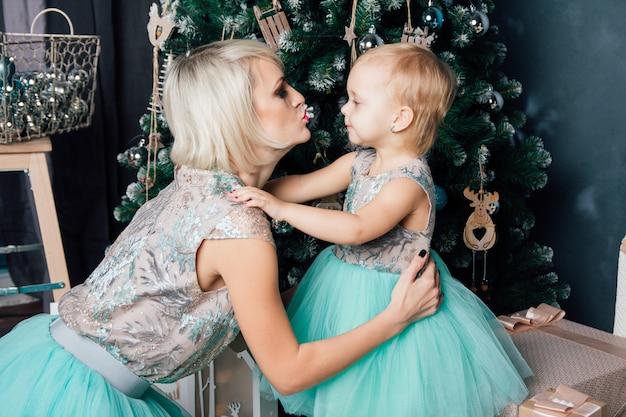 Moeder en kleine dochter poseren in het nieuwe jaar interieur