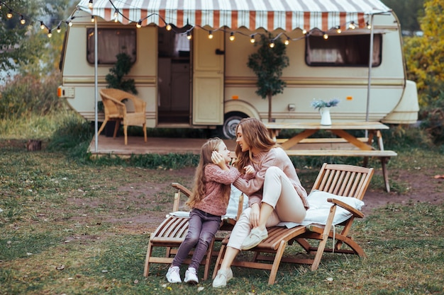 Moeder en kleine dochter zoenen en plezier maken op het platteland op camper van vakantie