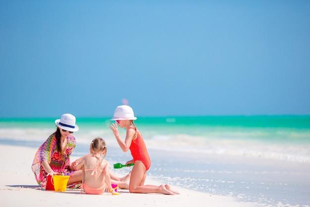 Moeder en kleine dochters die zandkasteel maken bij tropisch strand