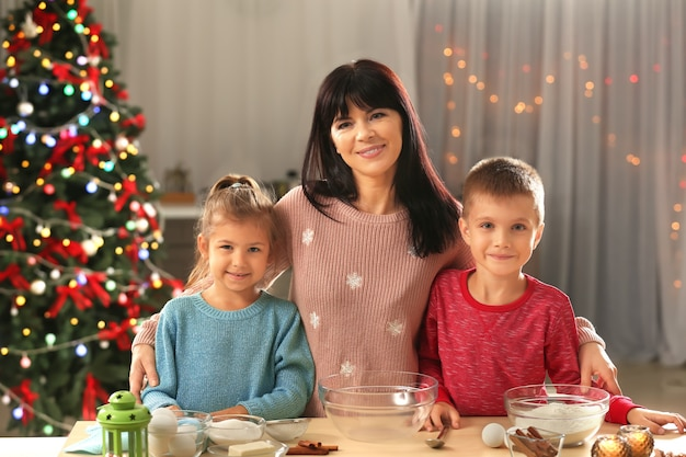 Moeder en kleine kinderen die kerstkoekjes maken in de keuken