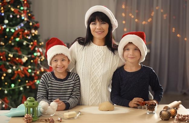 Moeder en kleine kinderen kerstkoekjes maken in de keuken