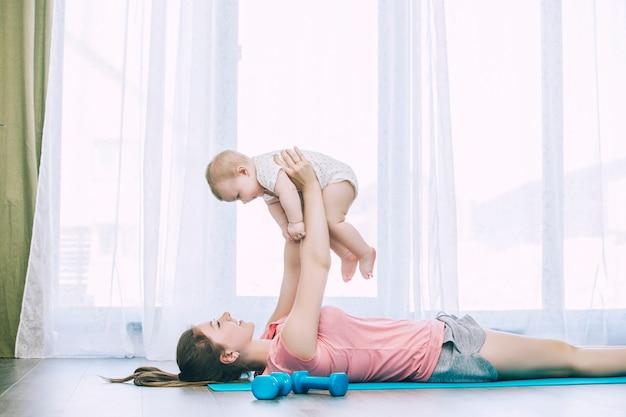 Moeder en kleine peuter doen fitness thuis op een oefeningsmat samen en lachend thuis