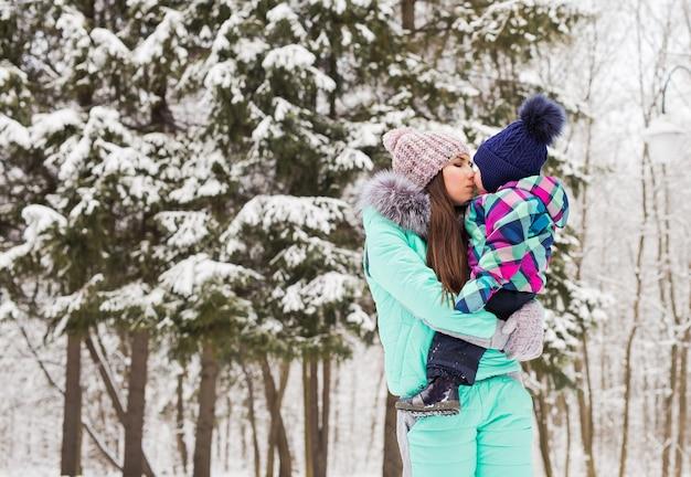 Moeder en kleine peuterjongen wandelen in het winterbos en hebben plezier met sneeuw. familie genieten van de winter. kind en vrouw kijken naar vallende sneeuw buitenshuis. winter, kerst en lifestyle concept.