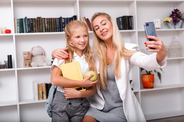 Moeder en kleine schattige dochter nemen selfies thuis, poseren voor de camera voordat ze naar school gaan