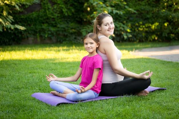 Moeder en lachende dochter beoefenen yoga en zitten rug aan rug in het park