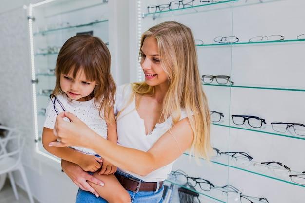 Moeder en meisje bij opticienwinkel