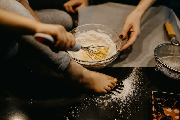 Moeder en meisje die bloem met eieren mengen, deeg voor koekjes maken