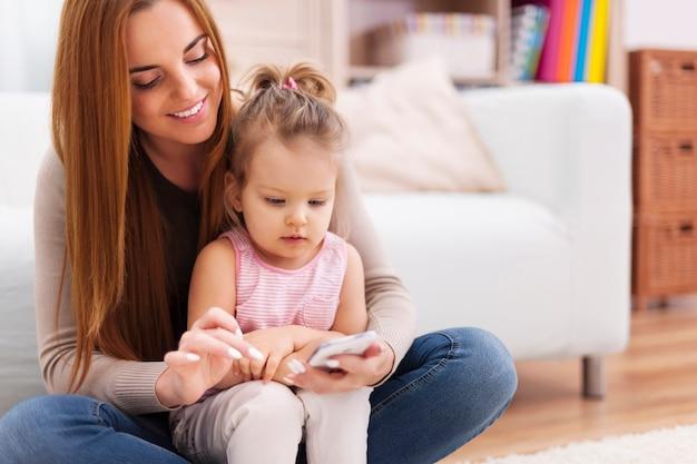 Moeder en meisje die mobiele telefoon thuis met behulp van